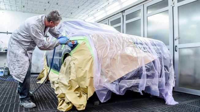 Werkstattmeister lackiert Front eines PKW
