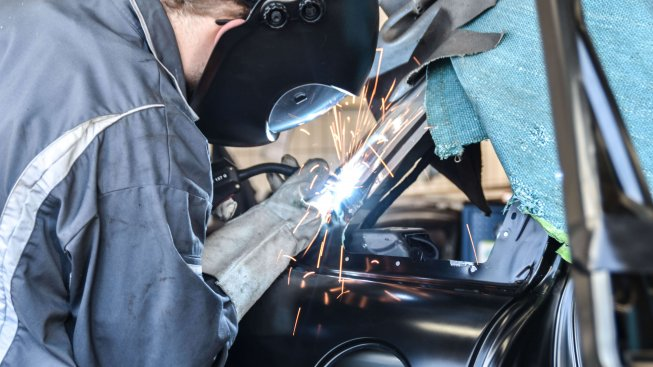 Werkstattmeister schweißt an Karosserie eines Unfallautos